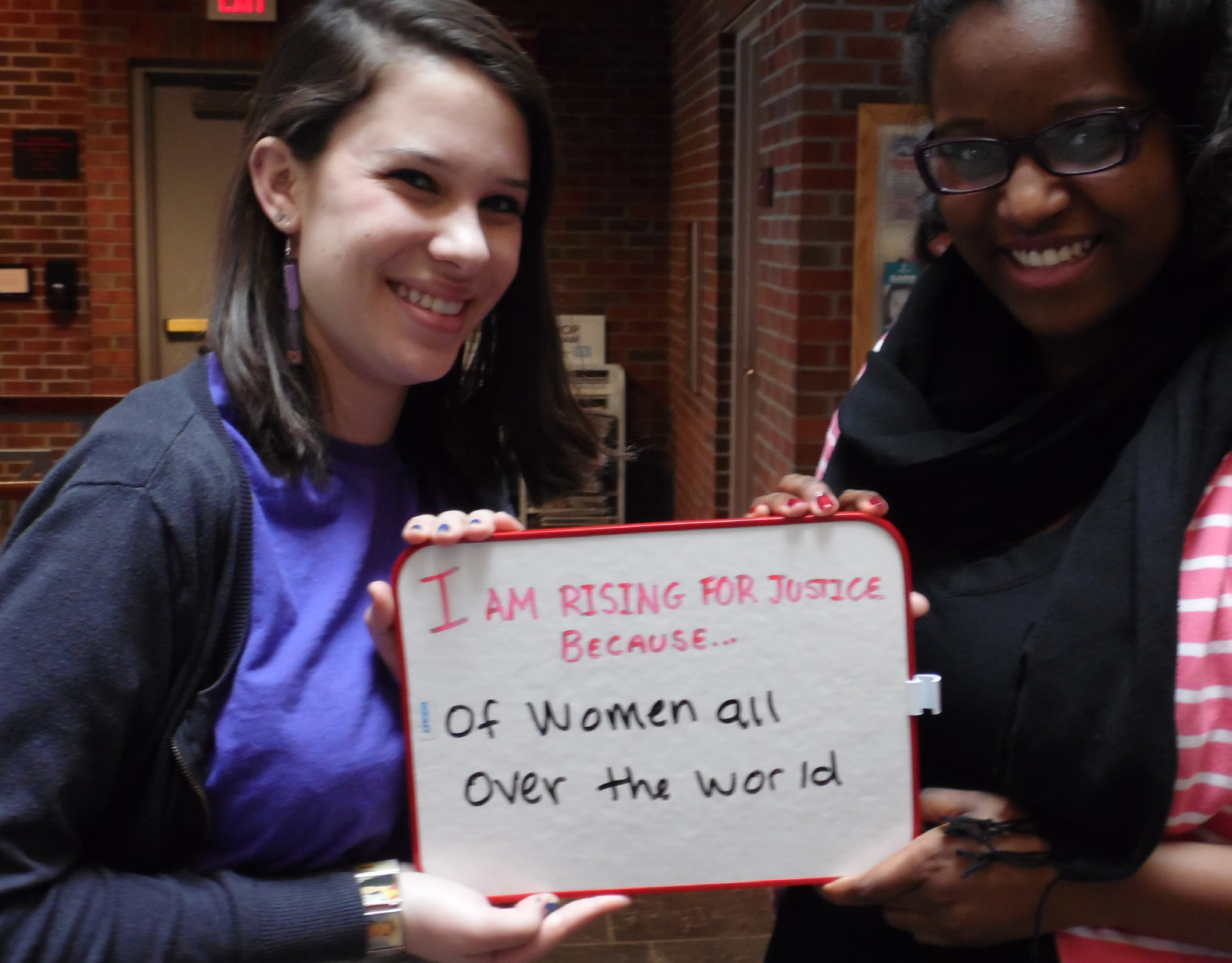"""Juniors Anji Herman (left) and Brianna Robinson hold a sign together. Herman helped plan the event, and Robinson and junior Felicia Rose read """"One Billion Rising for Justice"""" by Eve Ensler."""