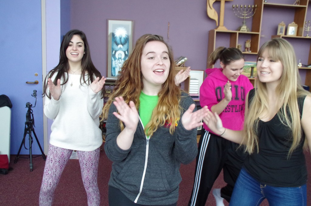 "Left to right: Freshman Zoe Sares, senior Grace Thompson, junior Emily Slee and sophomore Abi Horvat clap during ""Boy Band Mashup."""