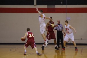 Sophomore wing Ben Simpson jumps past Oberlin guard Ian Campbell. Photo courtesy of Spenser Hickey.