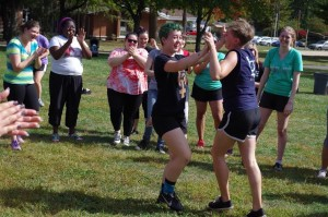 Rowan Hannan (left) and Meredith Harrison celebrate after winning a tug of war match at Delta Zeta's fall philanthropy event, while fellow Women's House residents clap in the background. Photo courtesy of Spenser Hickey.