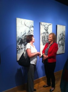 "Attendees talk in front of Caroline Bodee's ""Egotism"" series. Photo courtesy of Adelle Brodbeck."