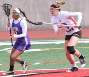 Freshman Kelsey Bowling rushes to defend a Capital attacker in a recent loss to the Crusaders. Photo by Leia Mizas.