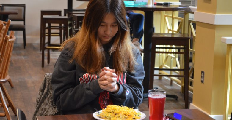 Wang prays quietly before eating her American meal.