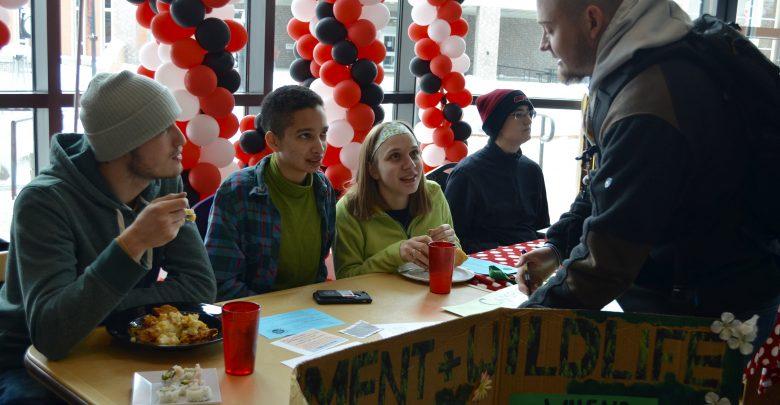 Dustin Braden, Nina Codrington-White, Annie Vitti explaining to Warren Bull their organization.