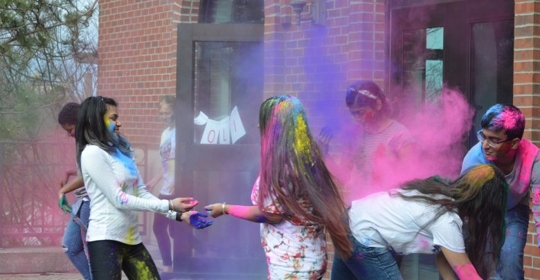 OWU students throw colorful powder at each other.