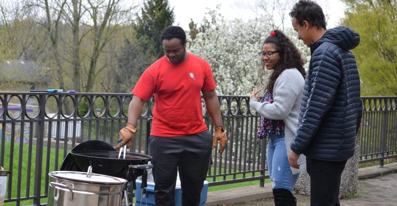 Isaiah Braithwaite prepared the grill as Zannalee Carling and Seth Roberts watch.