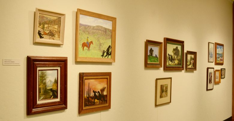 "The title is ""Salon de los Ilegales."" Some of Carlos Fresquez's art work displayed in Beeghly Library."